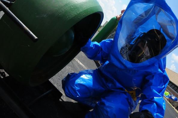 Senior Airman Michelle Schmitt, an Emergency Management Journeyman of the 107th Airlift Wing fixes a simulated leak a one-ton cylinder tank in her level-A  ensemble.