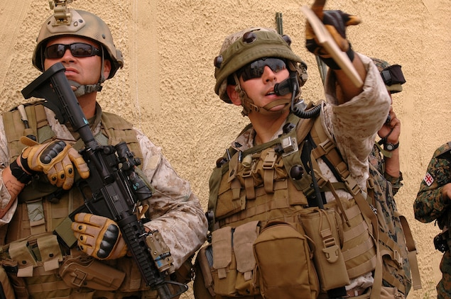 Master Sgt. Hector Reyes {LEFT}, team chief, Georgia Liaison Team, and Sgt. Christopher Holm examine the rooftop of a building in a simulated Afghanistan village. Both Marines are with 2d Air Naval Gunfire Liaison Company and are assisting with training the Georgian 32nd Light Infantry Battalion. The 32nd Light Infantry Battalion is the second of four battalions to undergo training through the Georgia Deployment Program, a Marine Corps-led initiative designed to prepare the Georgians for their upcoming Afghanistan deployment in support of International Security Assistance Forces there.
