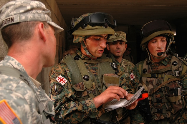 """Republic of Georgia Army 2nd Lt. Besik Kapanadze {CENTER}, 3rd Platoon leader, """"B"""" Company, 32nd Light Infantry Battalion, discusses the situational training exercise (STX) with an observer/controller with the Joint Multinational Readiness Center. The Republic of Georgia's 32nd Light Infantry Battalion was conducting cordon searches during their STX training. The STX is the first part of the mission rehearsal exercise, a final evaluation of the 32nd Battalion as they prepare for their deployment to Afghanistan in support of International Security Assistance Forces there."""