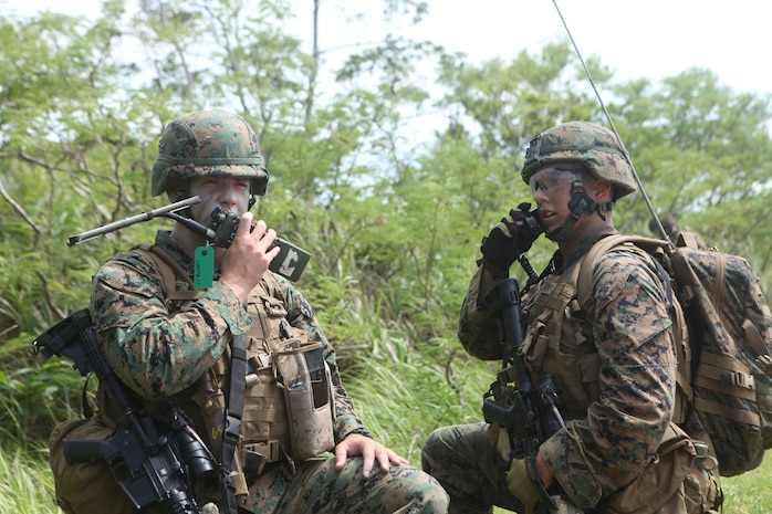 1st Lt. Justin Bokert (left), platoon commander with Company C, Battalion Landing Team 1st Battalion, 7th Marines, 31st Marine Expeditionary Unit, communicates to a forward squad on his radio during a simulated helicopter raid at LZ Dodo, Aug. 12. The helo raid was in support of the 31st MEU's preparation for its fall patrol. (Official Marine Corps photo by Cpl. Michael A. Bianco)