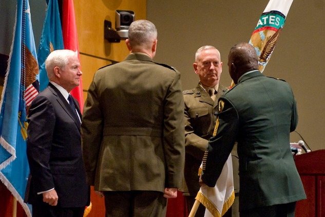 Incoming commander of U.S. Central Command Gen. James N. Mattis, takes the flag signifying the assumption of command from outgoing acting Lt. Gen. John Allen, center, while Defense Secretary Robert M. Gates looks on during an assumption of command ceremony at MacDill Air Force Base, Fla., Aug. 11, 2010.