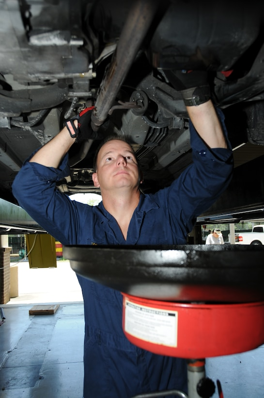 Chief Petty Officer Joel McEwen changes his oil at the auto hobby shop July 28.  The chief is assigned to the Supervisor of Shipbuilding in Pascagoula, Miss.  (U.S. Air Force photo by Kemberly Groue)