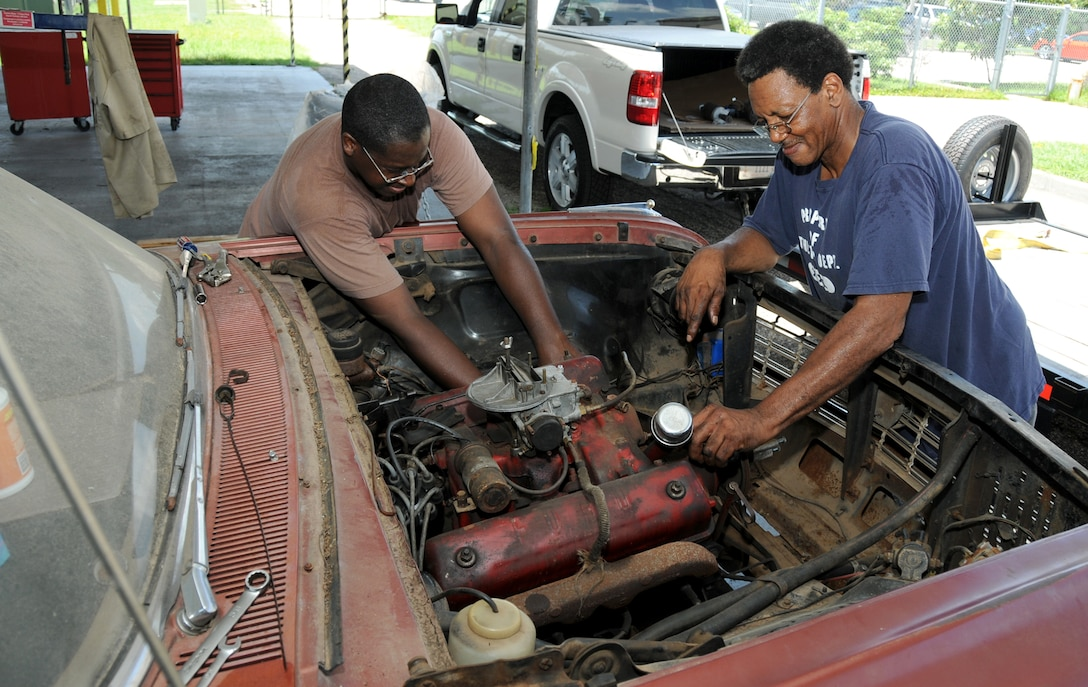 Master Sgt. Patrick Key, left, 81st Logistics Readiness Squadron, is getting his hands dirty with his dad, Albert Key, who's on vacation from Canton, Miss.  They're restoring a 1962 Ford Galaxy in one of the covered storage units behind the shop.  (U.S. Air Force photo by Kemberly Groue)
