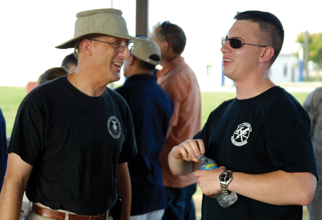 During a recent steak cookout at the Latte' Lounge in the dorm area, chapel volunteers and staff cooked and served and visited with residents.  Wing Chaplain (Lt. Col.) David Terrinoni, talks with Airman 1st Class Chris Rowland, a family practice medic in the 72nd Medical Group. (Air Force photo by Margo Wright)