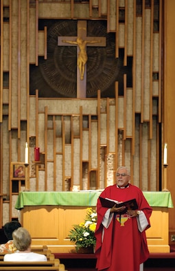 Daily Mass offers base Catholics a mid-day spiritual uplift.  Leading the service Aug. 10, Father Manuel Magallanes wears a red vestment, signifying martyrs, during the Feast of St. Lawrence.  Father Magallanes is from St. Gregory's Abbey in Shawnee and supports the Tinker Base Chapel Catholics by sharing service work with other Catholic chaplains. (Air Force photo by Margo Wright)