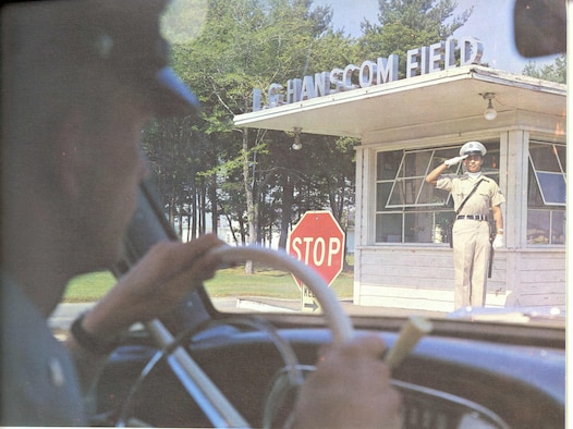 An Airman salutes as personnel drive on to Hanscom Field in 1966. (U.S. Air Force photo)