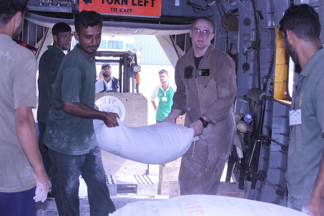 Cpl. Donald Cutler, a member of the HMM-165 reinforced (REIN), 15th Marine Expeditionary Unit assists local Pakistani citizens with loading food onto a Marine Super Stallion (CH-53E) as a part of humanitarian relief efforts in Pakistan, Khyber Pakhtunkhwa province (formerly North West Frontier province), Pakistan, Aug. 13, 2010.