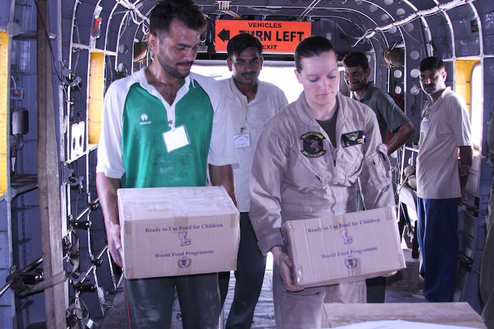 U.S. Marine Sgt. Jill Wells, a member of the HMM-165 reinforced (REIN), 15th Marine Expeditionary Unit assists local Pakistani citizens with loading food onto a Marine Super Stallion (CH-53E) as a part of humanitarian relief efforts in Pakistan, Khyber Pakhtunkhwa province (formerly North West Frontier province), Pakistan, Aug. 13, 2010.