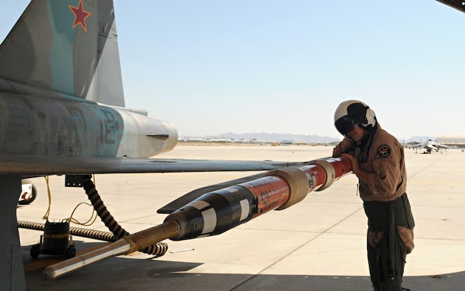 Maj. Chris Holloway, Marine Fighter Training Squadron 401 pilot, checks the placement of a tactical combat training system pod on an F-5E Tiger aircraft prior to takeoff at the Marine Corps Air Station in Yuma, Ariz., Aug. 13, 2010. The pod allows the TCTS to track the movement and weapons systems of the aircraft while taking part in training exercises.