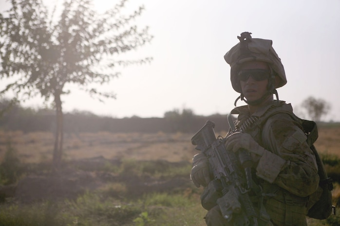 Lance Cpl. Taylor M. Boyd, a squad automatic weapon gunner with Echo Company, 2nd Battalion, 6th Marine Regiment, checks on his squadmates during a patrol through Marjah, Afghanistan, Aug. 15, 2010. Boyd, 19, is from Ellenboro, N.C.