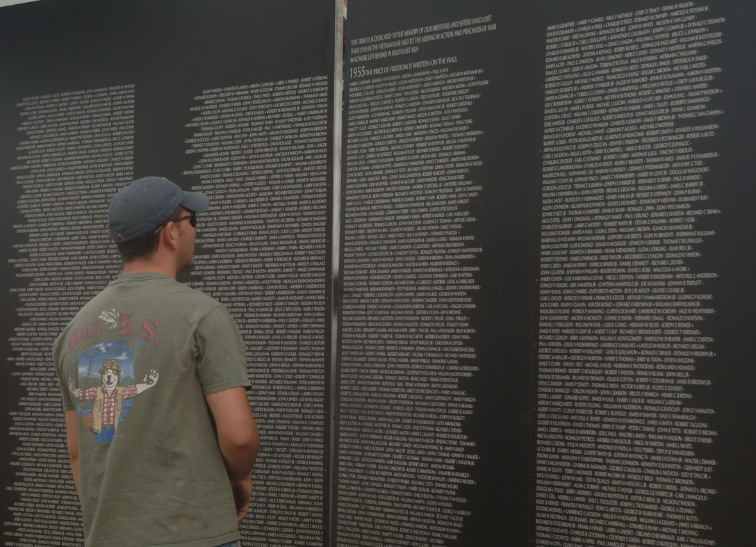 ELLSWORTH AIR FORCE, S.D. – Airman 1st Class John Weaver, 28th Maintenance Squadron aircraft fuel systems maintainer, pauses for a moment to read some of the names on the traveling wall in the Buffalo Chip, Sturgis, S.D., Aug. 8.  The traveling wall contains all of the names on the original Vietnam Memorial Wall. (U.S. Air Force photo/Airman 1st Class Alessandra N. Hurley)