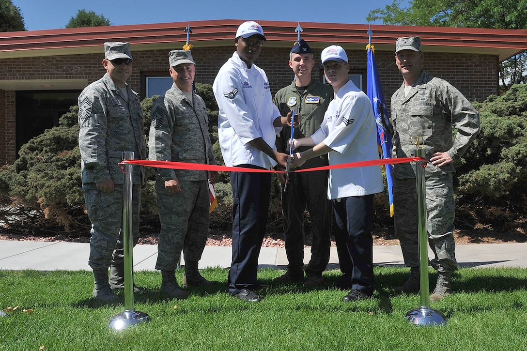 Col. Stephen N. Whiting, 21st Space Wing commander (center) is flanked by Airman 1st Class Derek Woolbright-Hutchins (left) and Airman 1st Class Brandon Gillespie, both dining hall staffers, to cut the ribbon for the official grand reopening of the Aragon dining facility Aug. 6. The dining hall had been closed since April while it was renovated with a new heating, ventilating and air conditioning unit, new restroom facilities, a handicap accessible doorway and a new, modern motif. (U.S. Air Force photo/Rob Bussard)