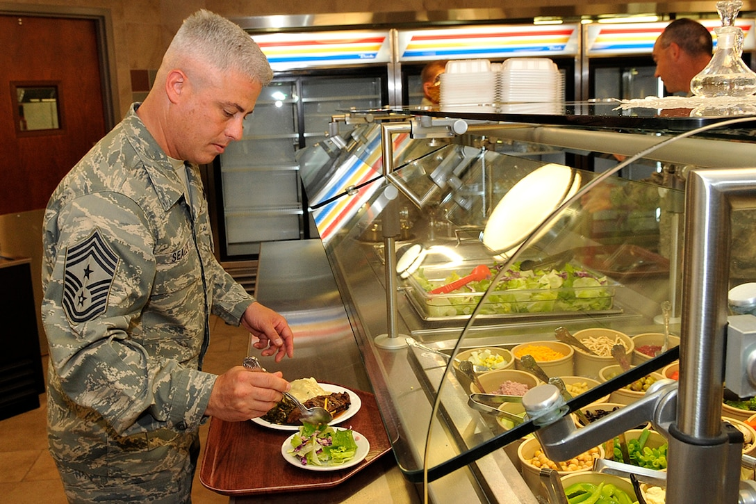 Chief Master Sgt. Robert Sealey, 21st Space Wing command chief, serves himself lunch at the Aragon dining facility Aug. 6 following a grand reopening celebration. The dining facility had been closed since April for a renovation project that including replacing the heating, ventilating and air conditioning unit, overhauling the restrooms and remodeling the dining area with a fresh, modern look. (U.S. Air Force photo/Rob Bussard)