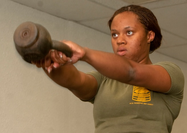 Cpl. Ashley Perkins, a graphics reproduction specialist with Combat Camera, U.S. Marine Corps Forces, Pacific,  demonstrates how to properly use kettle bells to stay physically fit while minimizing the risks of injury Aug. 18 during the MarForPac Health and Wellness Fair at the MarForPac headquarters building, here. The event was intended to raise health awareness and introduce programs Marine Corps Community Services offers to manage stress and stay physically fit.