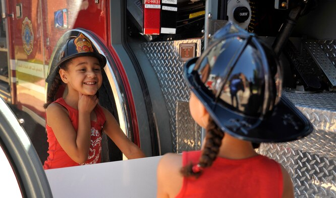 Billie Evans looks at her reflection in a chrome panel of one of the fire trucks on display at the Air Force Academy Fire Department's open house Aug. 14, 2010, at Fire Station 1. (U.S. Air Force photo/Bill Evans)