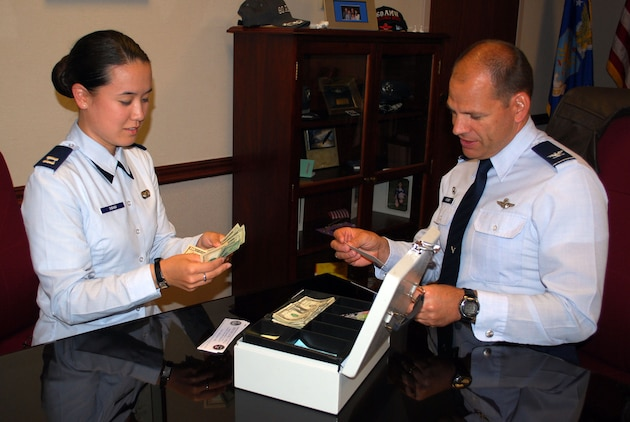 Col. James Vechery, 60th Air Mobility Wing commander, buys his tickets to the Air force Ball from Capt. Vanessa Swan, 60th Air Mobility protocol chief. The Air Force Ball is an event scheduled Sept. 18 that celebrates the birth of the Air Force. (U.S. Air Force photo/ Capt. Melissa Milner)