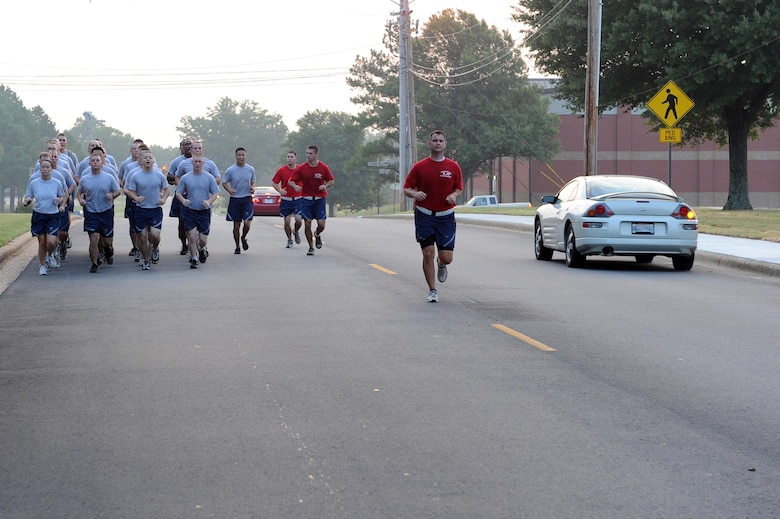 Airman Leadership School Airmen and instructors run in formation Aug. 20 during their morning physical training on base. Drivers on the roads must slow down to 10 miles per hour when passing formations. (U.S. Air Force photo by Senior Airman Steele C. G. Britton)