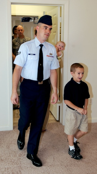 BARKSDALE AIR FORCE BASE, La. -- Airman 1st class Gary Boston and six-year-old son Gary Boston Jr., walks into their new home for the very first time Aug. 18. The Boston family is one of 97 families to move into the newly built duplex homes located in Liberty Heights on the East Reservation of base. (U.S. Air Force photo by Senior Airman La'Shanette V. Garrett) (RELEASED)