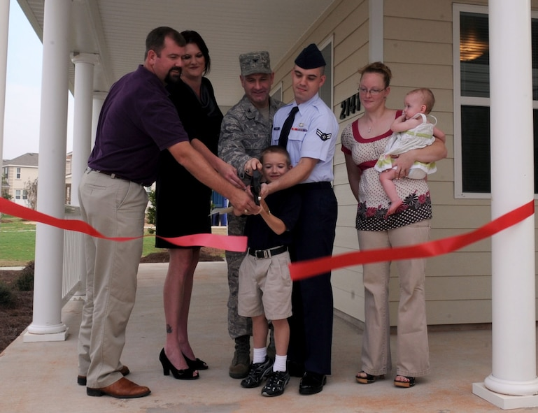 BARKSDALE AIR FORCE BASE, La. --  (From left to right) Matt Hoel, Hunt project manager, Elizabeth Kirkpatrick, Pinnacle investor and Col. Timothy Fay, 2d Bomb Wing commander assist the Boston family, Airman 1st class Gary and Helena, children Gary Jr., 6 and Annie, 11months, wtih the ribbon cutting of their newly three bedroom duplex home Aug. 18.The Boston family is one of 97 families to move into the Liberty Heights housing area. (U.S. Air Force photo by Senior Airman La'Shanette V. Garrett) (RELEASED)