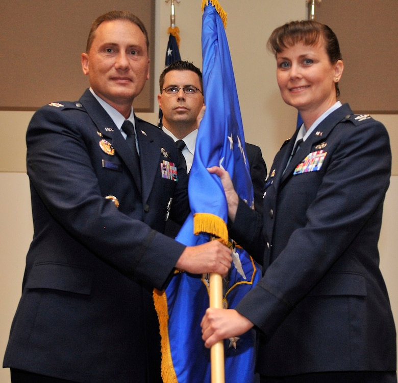 Col. Clint Crosier, 460th Space Wing commander, passes the 460th Mission Support Group flag to Col. Deirdre Mahon as she assumes command of the group Aug. 16. Colonel Mahon comes to Buckley Air Force Base from the Defense Logistics Agency headquarters at Fort Belvoir, Va., where she served as the chief of the distribution operations division. (U.S. Air Force photo by Airman 1st Class Paul Labbe)