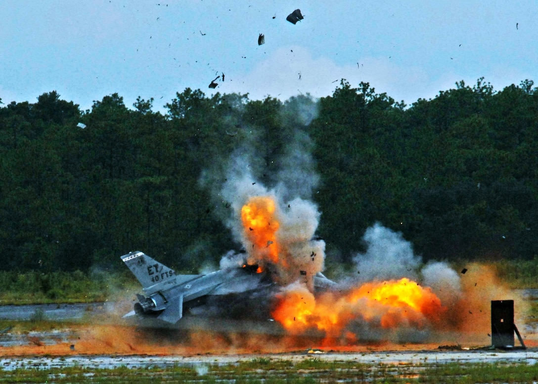 An F-16 Fighting Falcon explodes, sending debris and shrapnel into the air Aug. 19 on the Eglin Air Force Base range.  The explosion was a static test of the flight termination system to be used in the QF-16.  The purpose was to demonstrate that the FTS design will be sufficient to immediately terminate the flight of a QF-16, as well as determine a range safety debris footprint.  (U.S. Air Force photo/Samuel King Jr.)