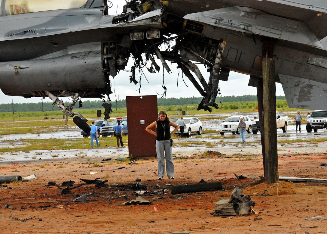 Beth Bartlett, test engineer for the flight termination system test, surveys the damage after the explosion  of an F-16 Fighting Falcon Aug. 19 at the Eglin Air Force Base range.   The explosion was a test of the FTS to be used in the QF-16.  The purpose was to demonstrate that the FTS design will be sufficient to immediately terminate the flight of a QF-16, as well as to determine a range safety debris footprint.  (U.S. Air Force photo/Samuel King Jr.)