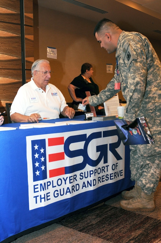 Army Spc. Roberto Mungaray talks about veterans' employment rights with Darren Venters from the Arizona Office of Employer Support of the Guard and Reserve, Aug. 21, at Tucson's first Yellow Ribbon Reintegration event. (Air Force photo by Maj. Gabe Johnson)