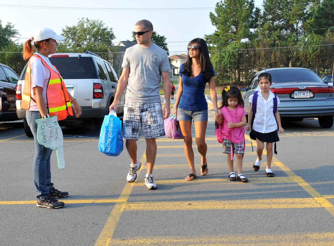 Staff Sgt. Christopher Whitten, 53rd Airlift Squadron flight engineer, and wife, Mechelle, walk daughters, Avalyn (left), 4; and Kaylee (right), 6; to school Aug. 19 with the help of a crossing guard. Crossing guards are posted at Arnold Drive Elementary School from 7:30 to 8:30 a.m. and from 3:50 to 4:15 p.m. to ensure the safety of the children crossing the streets. (U.S. Air Force photo by Staff Sgt. Chris Willis)
