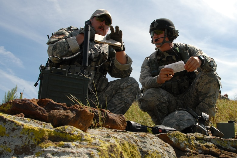 A1C Andrew Jundt listens as Lt. Col. Gary Nash directs an air strike on a nearby building during a close air support exercise Aug. 19 at Smoky Hill.
