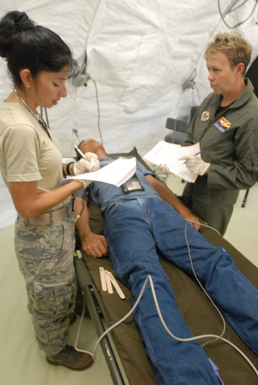 Lt. Col. Jackie Federico-Lopez, clinical nurse, 162nd Medical Group, Arizona National Guard, and Maj. Janet Campion, a flight surgeon also with the 162nd Med. Group, evaluate a victim during Vigilant Guard Guam, Aug. 24, 2010. The Airmen are part of the emergency medicine portion of the training exercise.  (U.S. Army photo by Sgt. Darron Salzer)