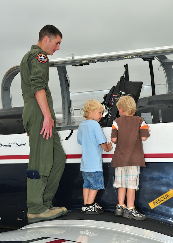 1st Lt. James Brantly from the 71st Flying Training Wing, Vance AFB, Oklahoma, gives young aviation enthusiasts an up close look at the T-6 Texan II trainer during the Volk Field Air National Guard Base open house on August 21, 2010. Despite inclement weather, the Volk Field Open house attracted approximately 3000 visitors, 20 military and civilian aircraft, numerous vendors, and aerial performers from across the country. (U.S. Air Force photo by Master Sgt. Paul Gorman)