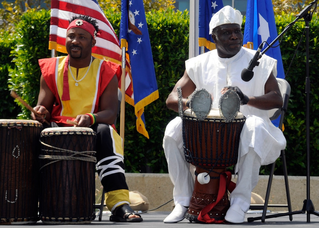 Two musicians drum to an African beat in one of the many music and dance performances during the Space and Missile Systems Center's first Diversity Day celebration in the Schriever Space Complex courtyard, Aug. 4.  The center set aside a major portion of the duty day to observe and acknowledge the cultural variety in its diverse workforce for this first-time event.  The organizers, entertainment and educational displays were all inclusive of a primarily volunteer effort.  Volunteers were from the local community as well as employees and Airmen from Los Angeles AFB.  (Photo by James Gordon)