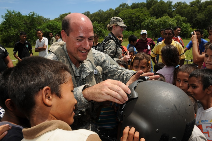 EL PICHICHE, El Salvador --  Dropping down the sunshade visor, Dr. (Col.) Michael Friedman, with the Joint Task Force-Bravo Medical Element, lets local children try on his helmet during the medical civic action program here Aug. 24. Team Bravo medical professionals assisted the El Salvador Ministry of Health and military in bringing medical care to more than 400 people in this remote village. (U.S. Air Force photo/Tech. Sgt. Benjamin Rojek)