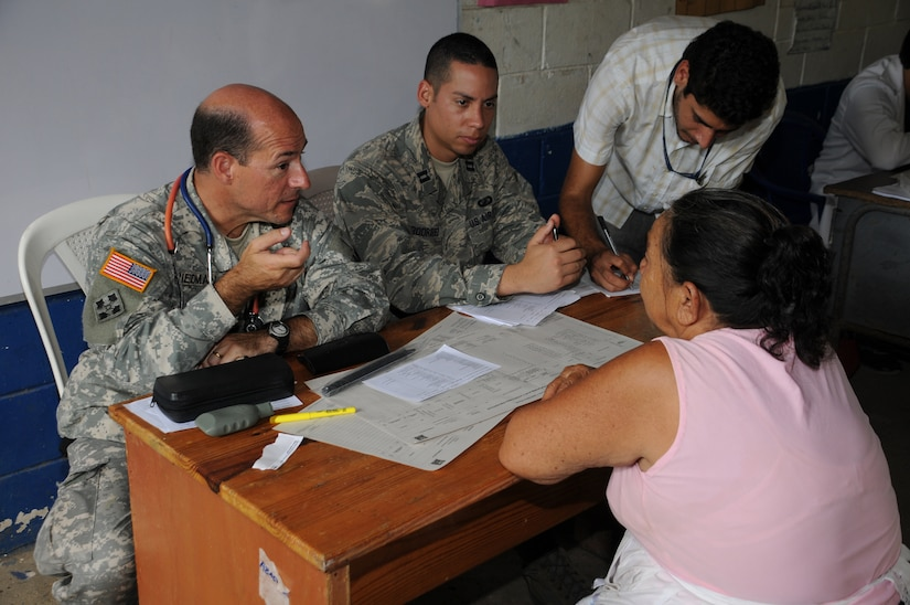EL PICHICHE, El Salvador --  Dr. (Col.) Michael Friedman, left, with the Joint Task Force-Bravo Medical Element, consults with patient as Capt. Javier Rodriguez, of the JTF-Bravo J3, helps translate during the medical civic action program here Aug. 24. Team Bravo medical professionals assisted the El Salvador Ministry of Health and military in bringing medical care to more than 400 people in this remote village. (U.S. Air Force photo/Tech. Sgt. Benjamin Rojek)