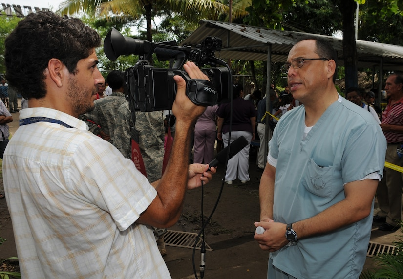 EL PICHICHE, El Salvador -- A journalist, left, interviews Dr. Guillermo Saenz, a Joint Task Force-Bravo Medical Element liaison officer, during the medical civic action program here Aug. 24. Dr. Saenz and other Team Bravo members assisted the El Salvador Ministry of Health and military in bringing medical care to this remote village. (U.S. Air Force photo/Tech. Sgt. Benjamin Rojek)