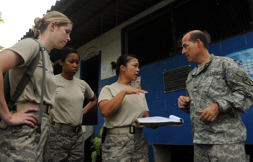 EL PICHICHE, El Salvador -- Shortly after arriving at the make-shift clinic site, 1st Lt. Nicole Musshorn, Senior Airman Jessica Keahey, Master Sgt. Judy Santa Ana-Christian and Dr. (Col.) Michael Friedman work out the day's traffic flow here Aug. 24 for a medical civic action program. The Team Bravo members assisted the El Salvador Ministry of Health and military in bringing medical care to this remote village, including preventative medicine and pharmacy care. (U.S. Air Force photo/Tech. Sgt. Benjamin Rojek)
