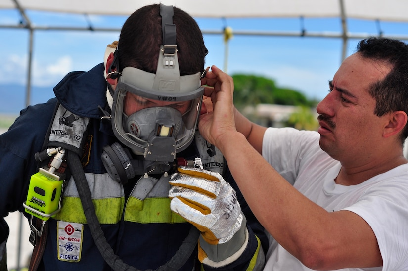 SOTO CANO AIR BASE, Honduras --  Jose Alberto Portillo, left, a firefighter from Tegucigalpa, Honduras, gets assistance from Henry Noj, a Guatemalan firefighter, in putting on his personal protective equipment during the Central America Sharing Mutual Operational Knowledge and Experiences exericse here Aug. 24. This year's firefighter training exercise included firefighters from Honduras, the 612th Air Base Squadron and, for the first time, Guetamala. (U.S. Air Force photo/Martin Chahin)