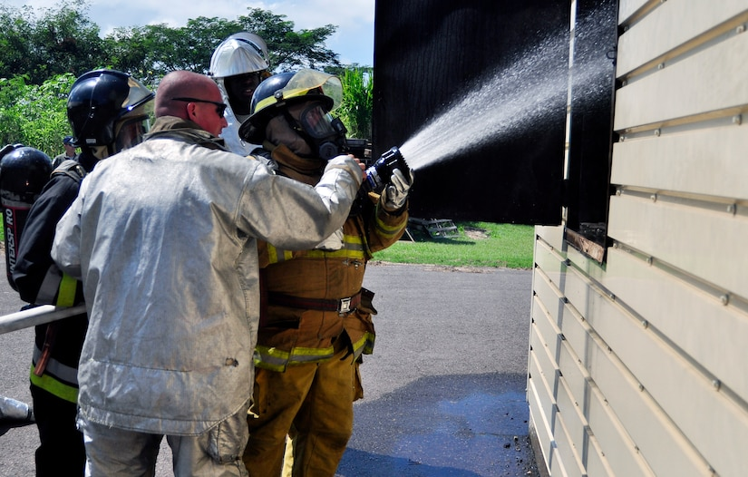 SOTO CANO AIR BASE, Honduras --  Spraying water through an open window, firefighters from the 612th Air Base Squadron train and train with Honduran and Guatemalan firefighters during the Central America Sharing Mutual Operational Knowledge and Experiences exericse here Aug. 26. This was the first time Guatemala participated in the annual exercise. (U.S. Air Force photo/Martin Chahin)