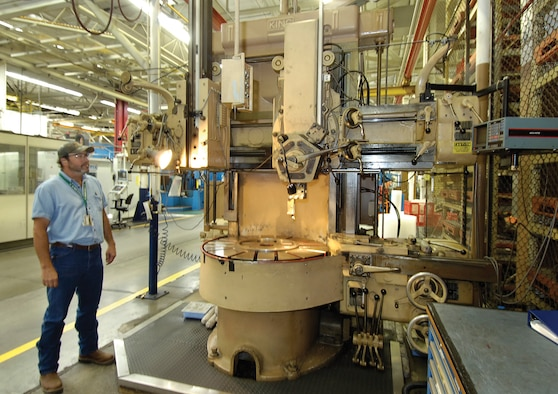 A King vertical turret lathe was installed in the industrial area of Bldg. 3001 in 1966. Work leader Kevin Greeson of the 548th Propulsion Maintenance Squadron, looks at the machine, one of several from the 60s and earlier that still work for the Air Force, often beside newer, highly computerized machines. (Air Force photo by Margo Wright)