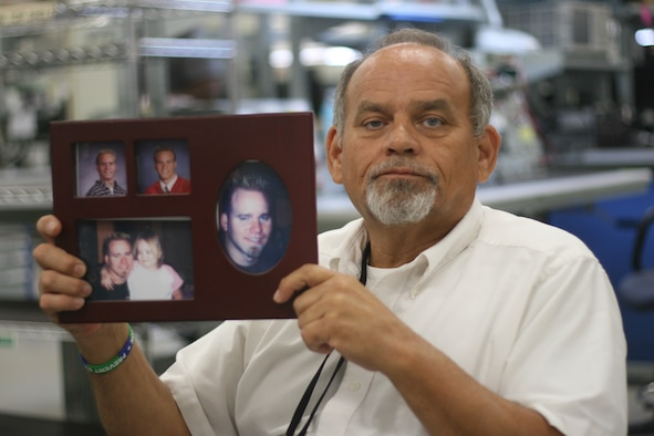 Rocky Dunham shows a picture of his son, Joey, who committed suicide more than two years ago. Since then, the tools and parts attendant in the 552nd Commodities Maintenance Squadron regularly speaks in the community about suicide prevention in the hope of sparing others from going through the pain of losing a loved one. (Air Force photo by John Stuart)