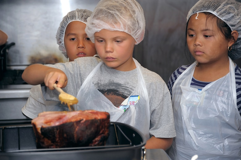 4-H culinary campers glaze a ham during the recent 4-H culinary camp. The campers learned about food preparation with the camp culminating in the eating of a meal of glazed ham, steamed snap peas and baked sweet potatoes prepared by the kids.  (Photo by Joe Juarez)