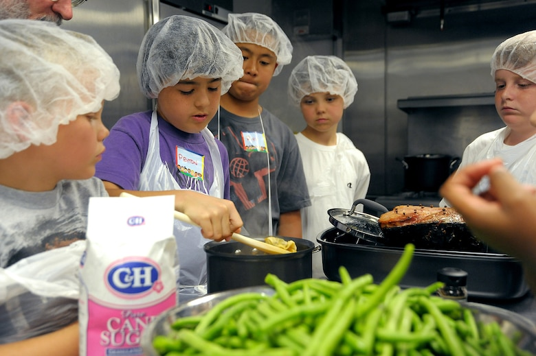 "4-H culinary campers work together to prepare a meal as part of the recent camp taught by Aaron Reaven from ""Chef-K.""  (Photo by Joe Juarez)"