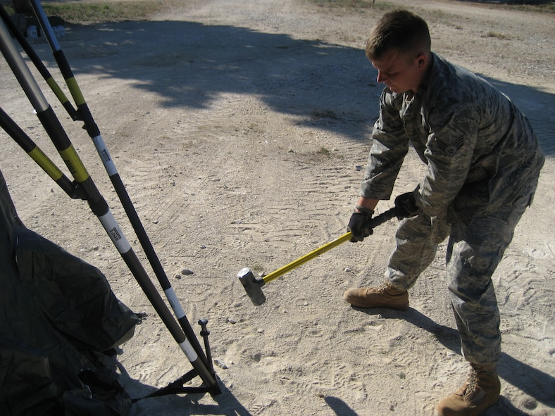 Senior Airman Ben Rasine, 1st Special Operations Civil Engineer Squadron J-Team, hammers a stake to secure a tent during Operation Jackal Stone in Croatia, September 2009. The J-Team is comprised of engineering specialists who enable special operations forces by providing resources to sustain their presence for weeks wherever they are required. (Courtesy photo from U.S. Air Force 1st Lt. Jeffrey Buchholtz)