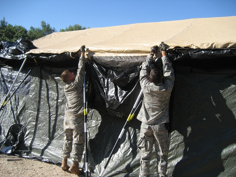 1st Lt. Jeffrey Buchholtz, right, and Senior Airman Ben Rasine, left, both 1st Special Operations Civil Engineer Squadron J-Team, secure a tent door during Operation Jackal Stone in Croatia, September 2009. The J-Team is comprised of engineering specialists who enable special operations forces by providing resources to sustain their presence for weeks wherever they are required. (Courtesy photo from U.S. Air Force Master Sgt. James Jarvis)