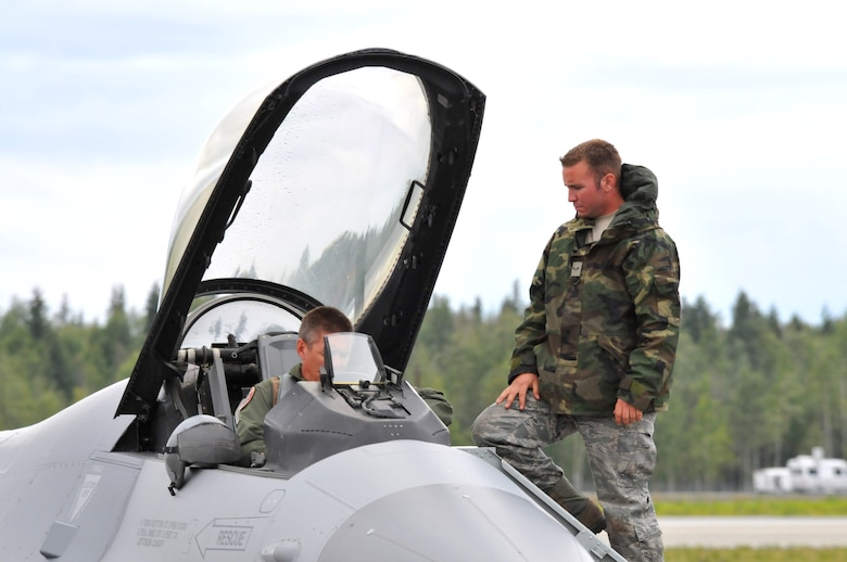 Airman 1st Class Jake Rasmussen, crew chief for the 115th Aircraft Maintenance Squadron, assists a pilot into the cockpit of the F-16 Fighting Falcon, during a Red Flag exercise, Eielson AFB, Alaska Aug. 18. Rasmussen deployed to Eielson in support of the 115th Fighter Wing out of Madison, Wis. (Wisconsin Air National Guard photo by Tech Sgt. Ashley Bell)