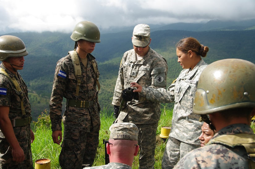 SOTO CANO AIR BASE, Honduras --  Sgt. 1st Class Allen King, Sgt. Delmi Quevedo, Sgt. Jason Myers and Spc. Salvador Nunez, all with the 1-228th Aviation Regiment, instruct Honduran soldiers on assembly and disassembly of the M2 at the Zambrano Range here Aug. 25. Proper assembly, maintenance, preliminary marksmanship instruction and firing techniques were taught by bilingual 1-228th Soldiers providing Honduran soldiers with a basic knowledge of both M2 and M249 weapons systems. (Photo courtesy of Capt. Thomas Pierce)