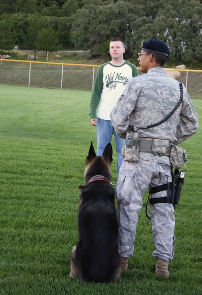 Members of the 21st Security Forces Squadron prepare to demonstrate apprehension tactics with one of their military working dogs for guests at the Deployed Families Dinner, hosted by Cheyenne Mountain Air Force Station Aug. 6. The event brought out nearly 120 guests despite thunderstorms and heavy rains, which cleared up as the event kicked off. (U.S. Air Force photo)