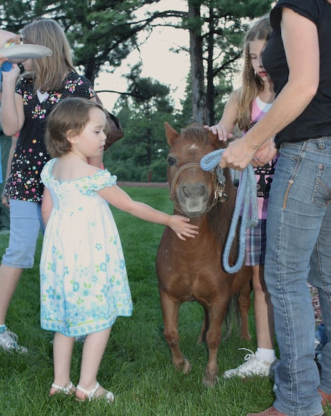 A young girl pets a miniature horse brought to the Deployed Families Dinner hosted by Cheyenne Mountain Air Force Station Aug. 6. Jackie Brusseau, 721st Mission Support Group contractor, along with her daughter, brought their two miniature horses for guests to pet and photograph. This was the first time the DFD was held at CMAFS. (U.S. Air Force photo)