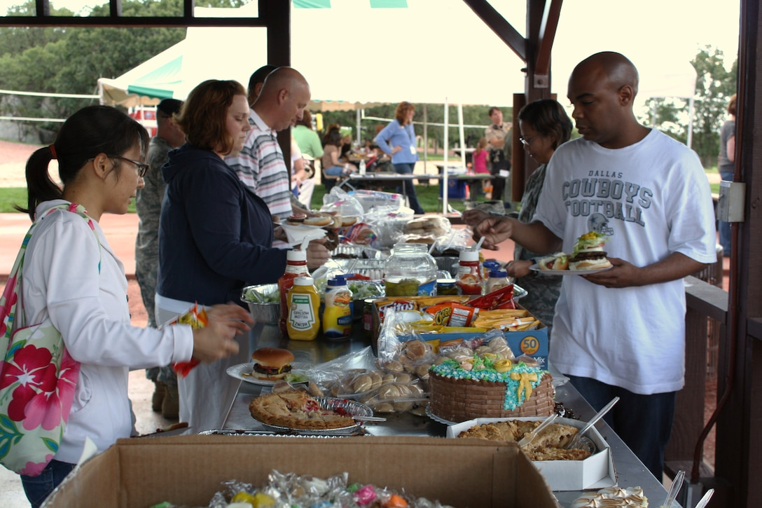 Event guests take part in free food at the Deployed Families Dinner, hosted by Cheyenne Mountain Air Force Station for the first time at Mountain Man Park Aug. 6. Families enjoyed free food, prizes, activities children and transportation to and from the event from Peterson Air Force Base. (U.S. Air Force photo)