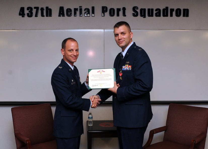 Capt. Nicholas Lee, right, is awarded the Bronze Star by Col. James Clavenna at the 437th Aerial Port Squadron on Joint Base Charleston, S.C., Nov. 22, 2010, for his meritorious service while deployed in a combat zone in support of Operation Enduring Freedom while assigned to the 1st Brigade, 201st Corps, in Afghanistan from May 7, 2009, to May 6, 2010. Captain Lee distinguished himself by serving in several key positions and personally commanding more than 70 mounted combat patrols covering 1,500 miles of contested Afghan terrain across nine provinces. His exploits included leading two Air Assault missions to set polling sites in a known Taliban safe haven, effectively securing more than 1,200 Afghan votes; planning and execution of three humanitarian aid missions, delivering 30,000 pounds of aid valued at $125,000; and command of a Mobile Response Force for three classified prisoner transfer missions. Colonel Clavenna is the 437th Maintenance Group commander, and Captain Lee is the 437th Aerial Port Squadron Cargo Flight commander. (U.S. Air Force photo/Senior Airman Timothy Taylor)